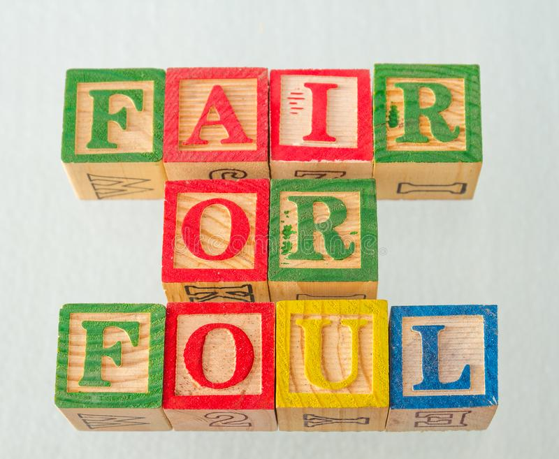The term fair or foul visually displayed. On a white background using colorful wooden blocks image in landscape format stock photos