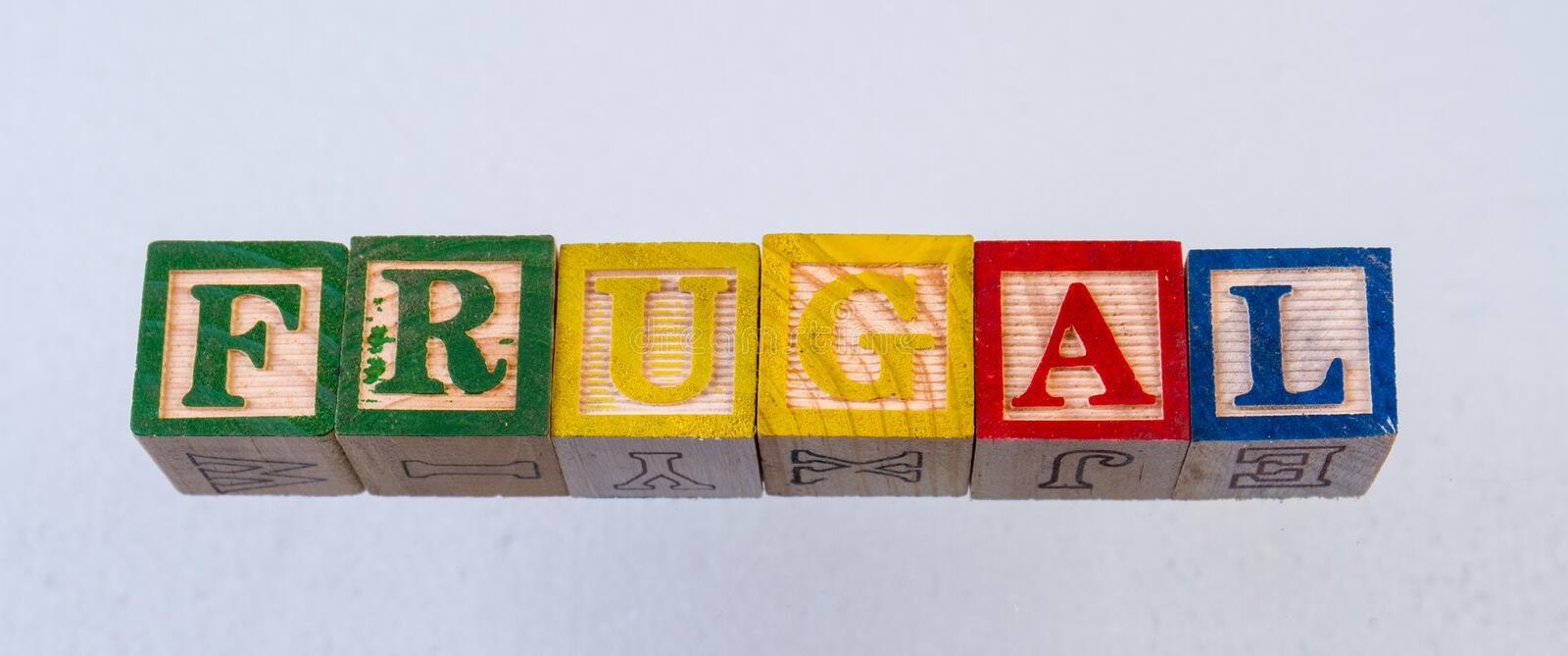 The term frugal visually displayed. On a white background using colorful wooden toy blocks royalty free stock photo