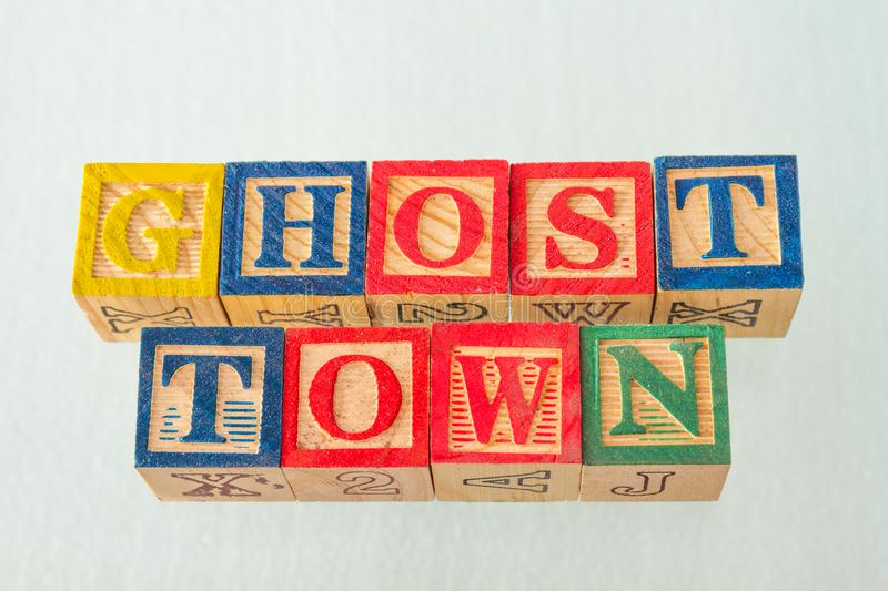 The term ghost town visually displayed. On a white background using colorful wooden blocks image in landscape format royalty free stock photography