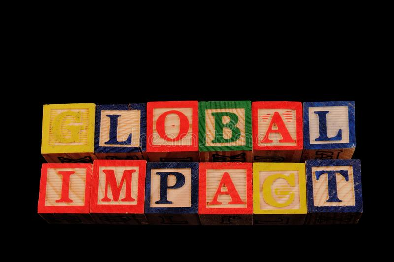 The term global impact visually displayed. On a black background using colorful wooden toy blocks image with copy space in landscape format stock image