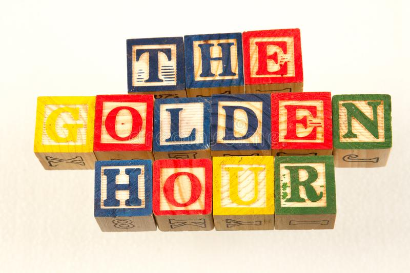 The term the golden hour visually displayed. The the term golden hour visually displayed using colorful wooden toy blocks on a white background image with copy royalty free stock images
