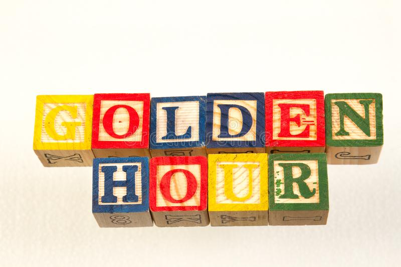 The term golden hour visually displayed. Using colorful wooden toy blocks on a white background image with copy space in landscape format stock images