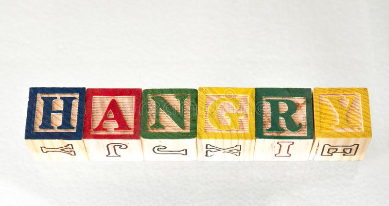The term hangry visually displayed. The term hangry displayed visually on a white background using colorful wooden toy blocks image with copy space in landscape royalty free stock image