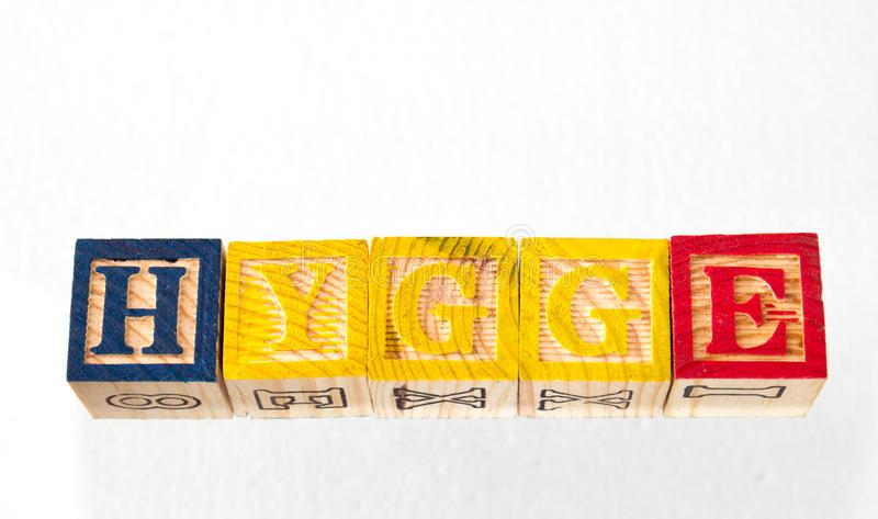 The term hygge visually displayed. On a white background using colorful wooden toy blocks image with copy space in landscape format stock photos