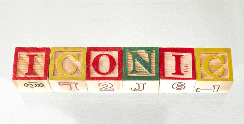 The term iconic visually displayed. The term iconic displayed visually on a white background using colorful wooden toy blocks image with copy space in landscape royalty free stock photo