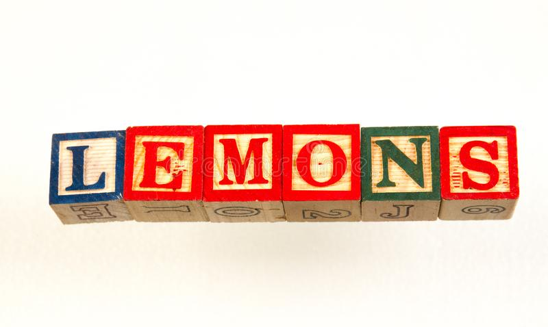 The term lemons visually displayed. Using colorful wooden toy blocks on a white background image with copy space in landscape format stock photo
