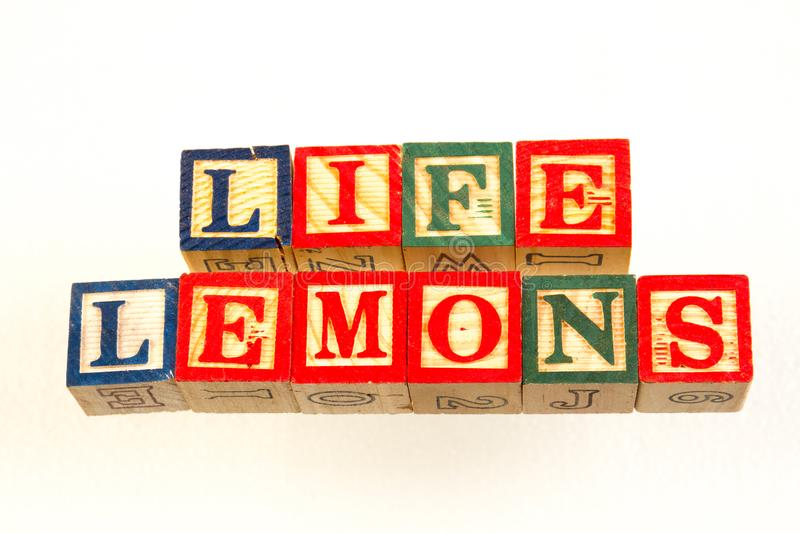 The term life lemons visually displayed. Using colorful wooden toy blocks on a white background image with copy space in landscape format royalty free stock photos