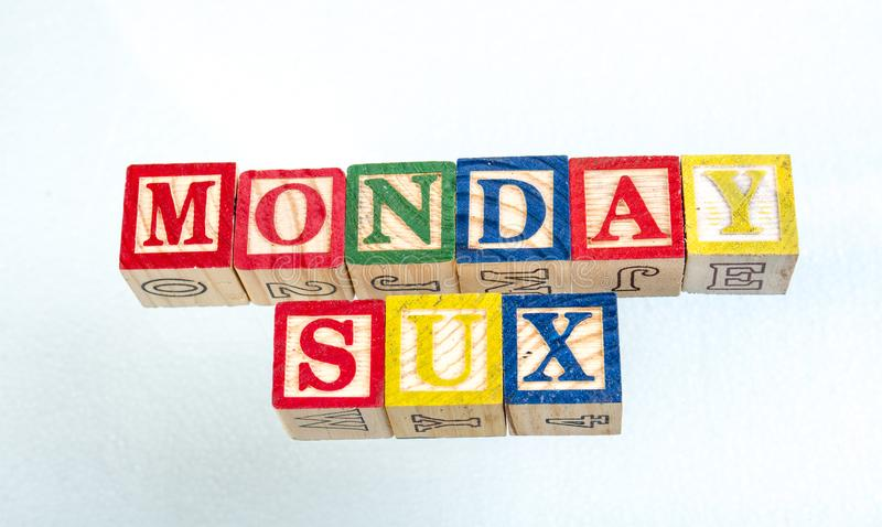 The phrase Monday sux displayed on a white background. The term Monday sux visually displayed on a white background using colorful wooden toy blocks image with stock images