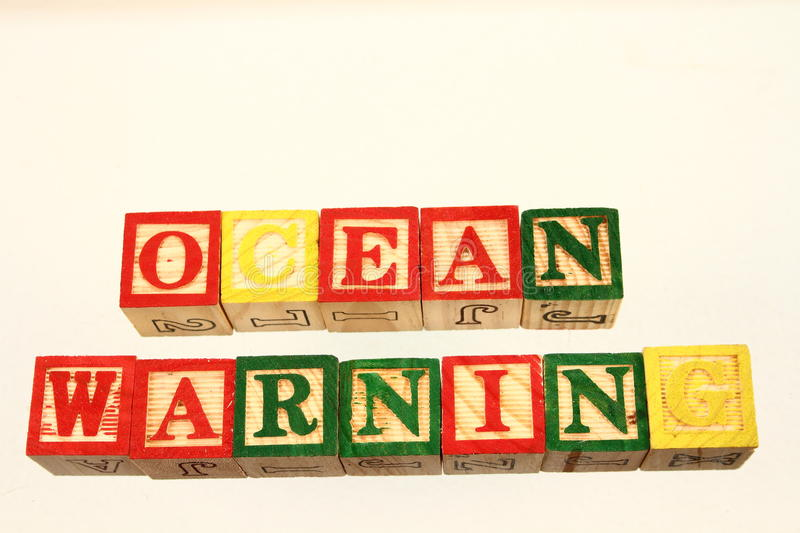 The term ocean warning. Displayed visually on a white background using colorful wooden toy blocks royalty free stock images