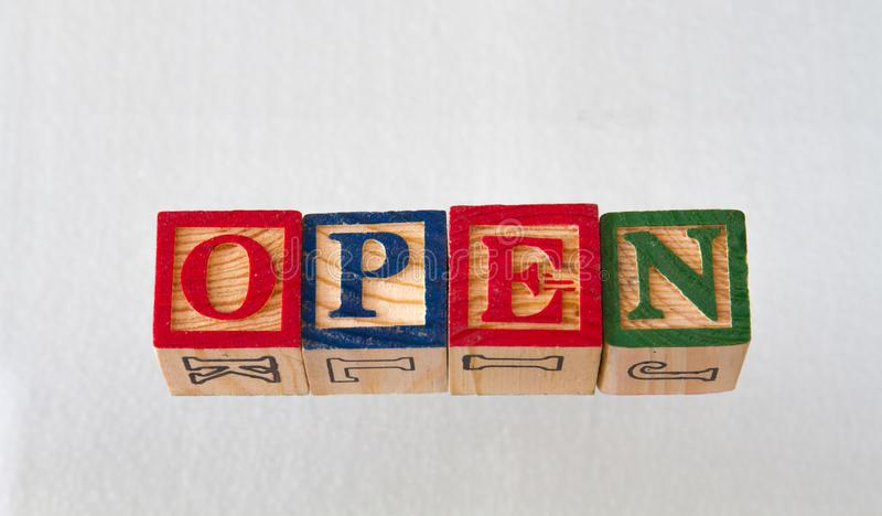 The term open visually displayed. In wooden toy blocks on a white background image with copy space in landscape format royalty free stock photo