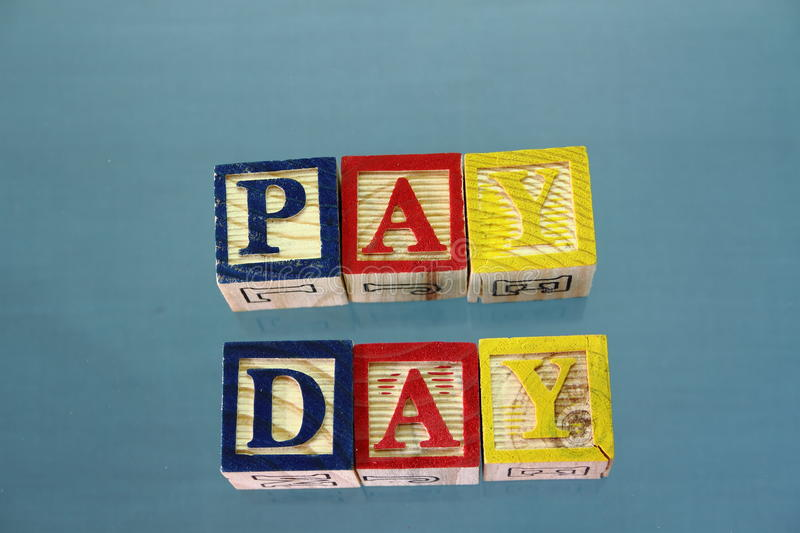 The term pay day. Displayed in a child`s wooden toy blocks on a clear blue surface stock photo
