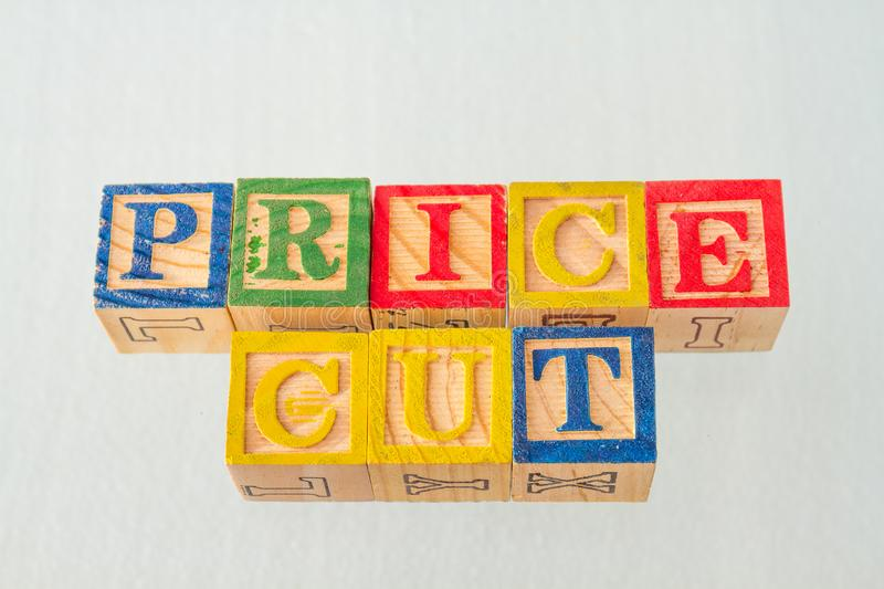 The term price cut visually displayed. On a white background using colorful wooden blocks image in landscape format stock photo