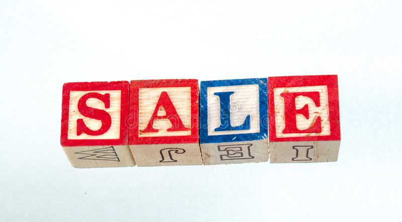 The phrase sale displayed on a white background. The term sale visually displayed on a white background using colorful wooden toy blocks image with copy space in royalty free stock images