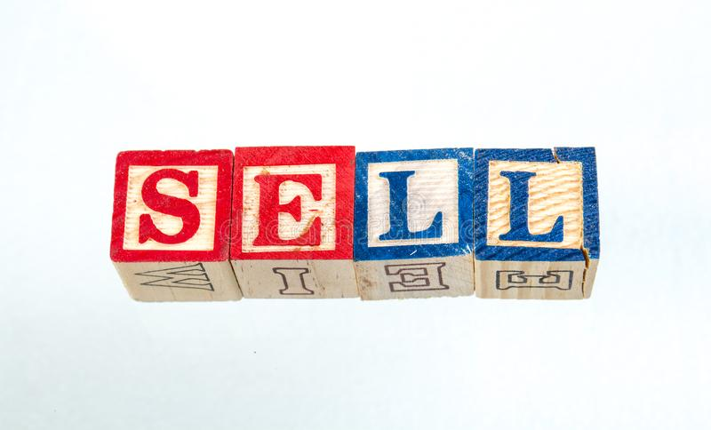 The phrase sell displayed on a white background. The term sell visually displayed on a white background using colorful wooden toy blocks image with copy space in royalty free stock photography