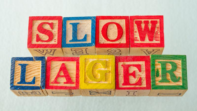 The term slow lager visually displayed. On a white background using colorful wooden blocks image in landscape format stock photos