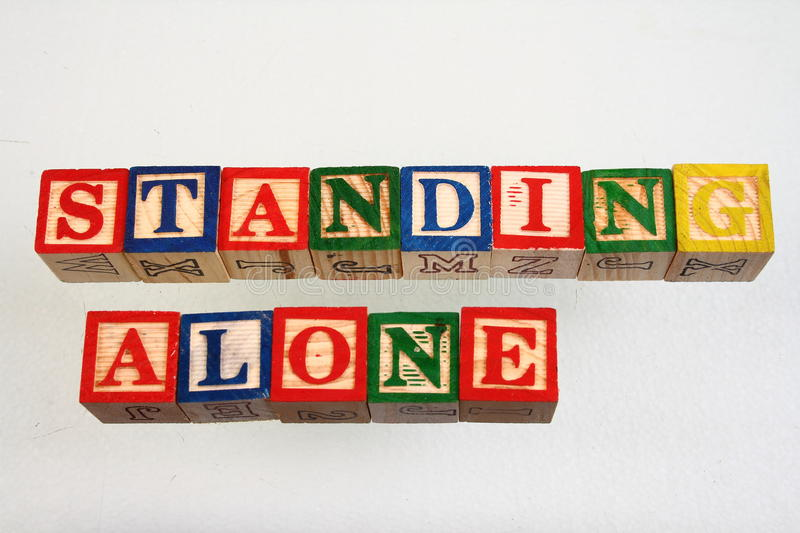 The term standing alone. Displayed visually using colorful wooden blocks on a white background in landscape format royalty free stock images