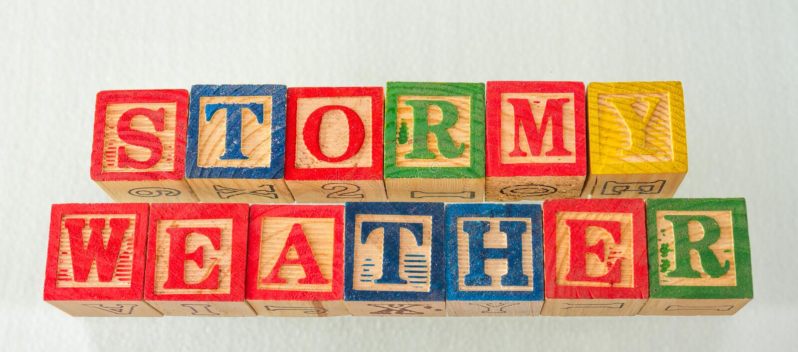 The term stormy weather visually displayed. On a white background using colorful wooden blocks image in landscape format royalty free stock images