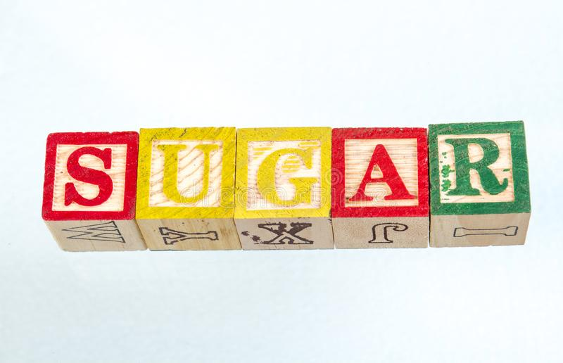 The phrase sugar displayed on a white background. The term sugar visually displayed on a white background using colorful wooden toy blocks image with copy space royalty free stock photos