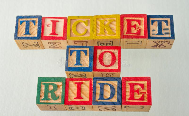 The term ticket to ride visually displayed. On a white background using colorful wooden blocks image in landscape format royalty free stock photography