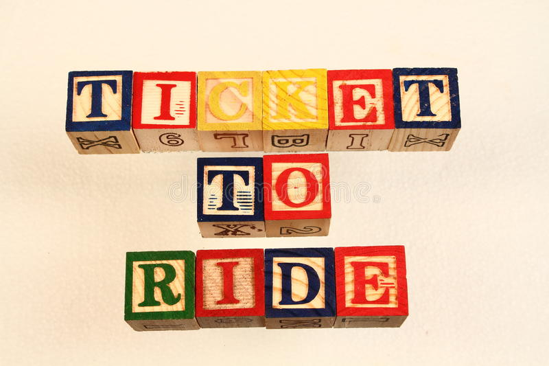 The term ticket to ride. Visually displayed on a white background using colorful wooden toy blocks in landscape format with copy space stock photography