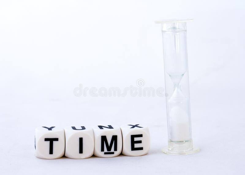 The term time on a white background - concept image. The term time in black text together with a hourglass isolated on a white background image with copy space stock images