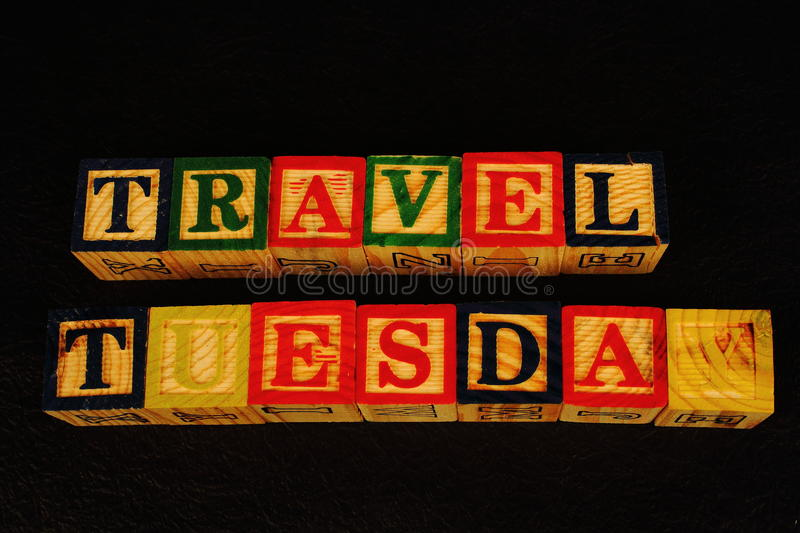 The term Travel Tuesday. Visually displayed on a black background in landscape format using colorful wooden blocks royalty free stock images