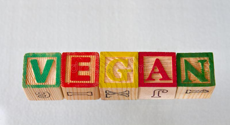 The term vegan visually displayed. In wooden toy blocks on a white background image with copy space in landscape format stock photo