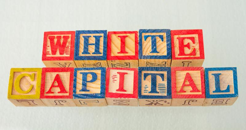 The term white capital visually displayed. On a white background using colorful wooden blocks image in landscape format royalty free stock photos