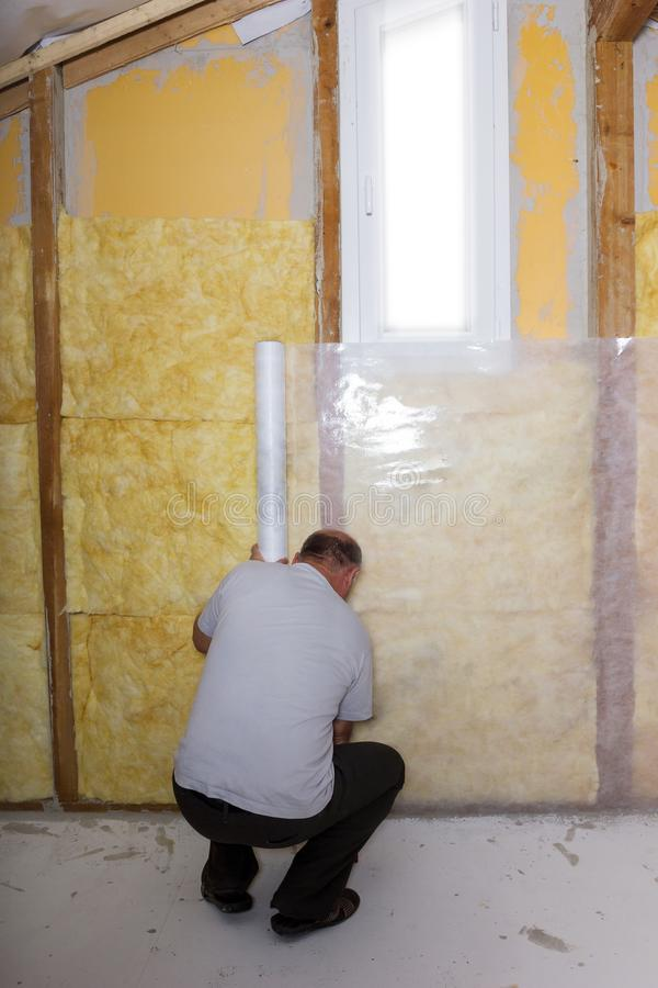 Termal insulation at the attic room. Handyman installing white r royalty free stock photo