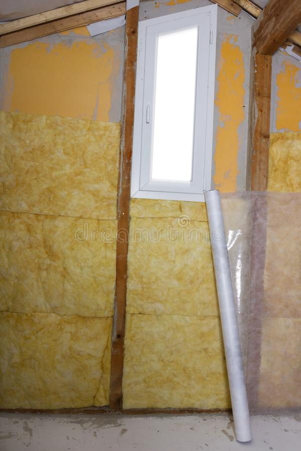 Termal insulation installing at the attic with white roll lean o royalty free stock images