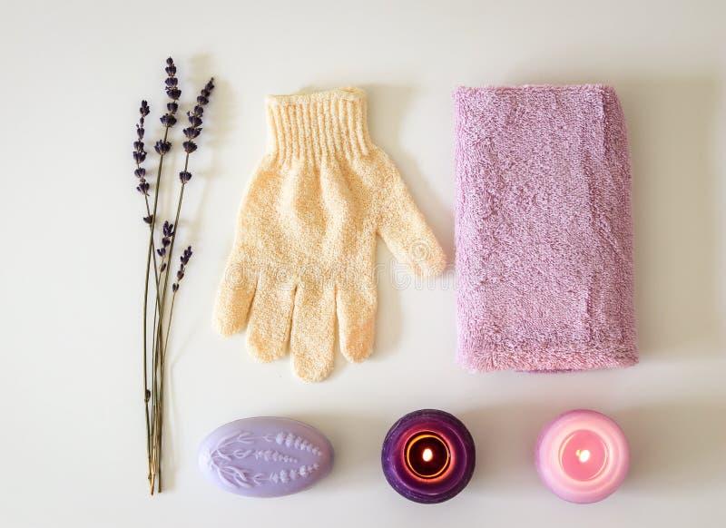 TERMAS ajustados com sabão da alfazema, a massagem exfoliating que descascam a luva, a toalha cor-de-rosa e velas roxas fotos de stock royalty free
