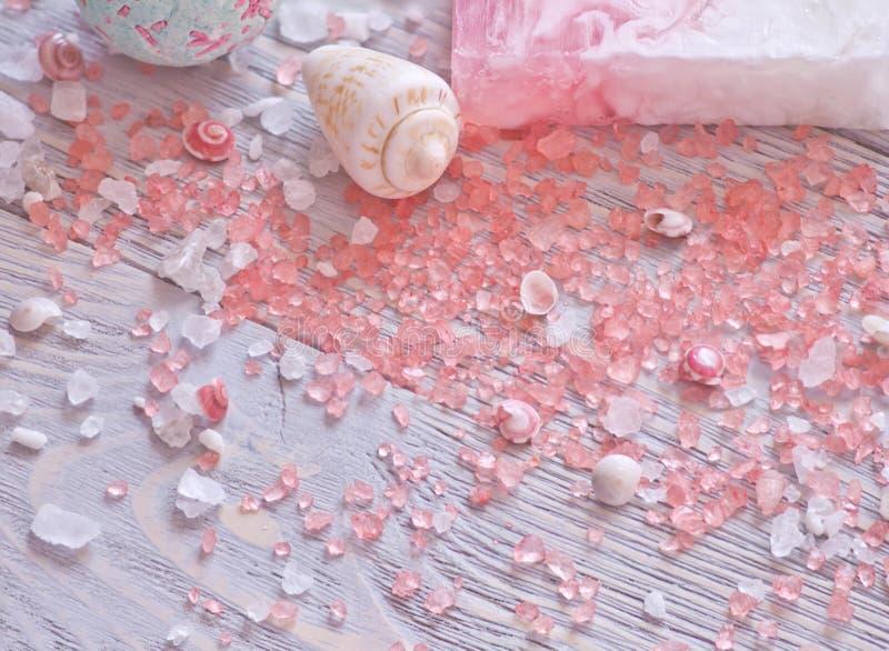 Termas e fundo da beleza Bomba do banho, barra feito a mão do sabão, conchas do mar e sal da aromaterapia em pranchas de madeira foto de stock