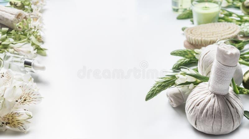 Termas e fundo do tratamento da beleza com as bolas ervais, as flores, as ferramentas e os acessórios da massagem no branco, quad fotografia de stock