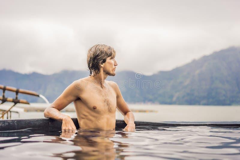 Termas geot?rmicas homem que relaxa na associa??o da mola quente Homem novo que aprecia o banho relaxado em uma lagoa da água azu fotografia de stock royalty free