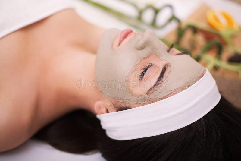 Termas A jovem mulher bonita está obtendo a máscara facial em termas, l da argila fotografia de stock royalty free