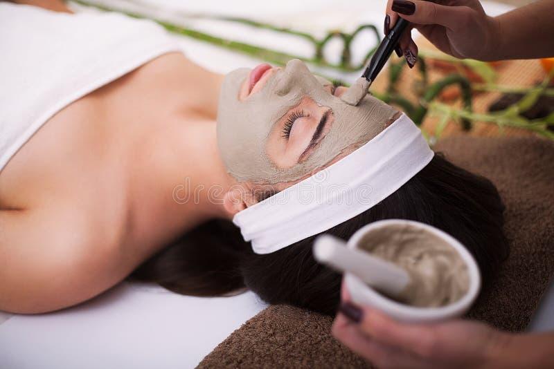 Termas A jovem mulher bonita está obtendo a máscara facial em termas, l da argila imagens de stock royalty free
