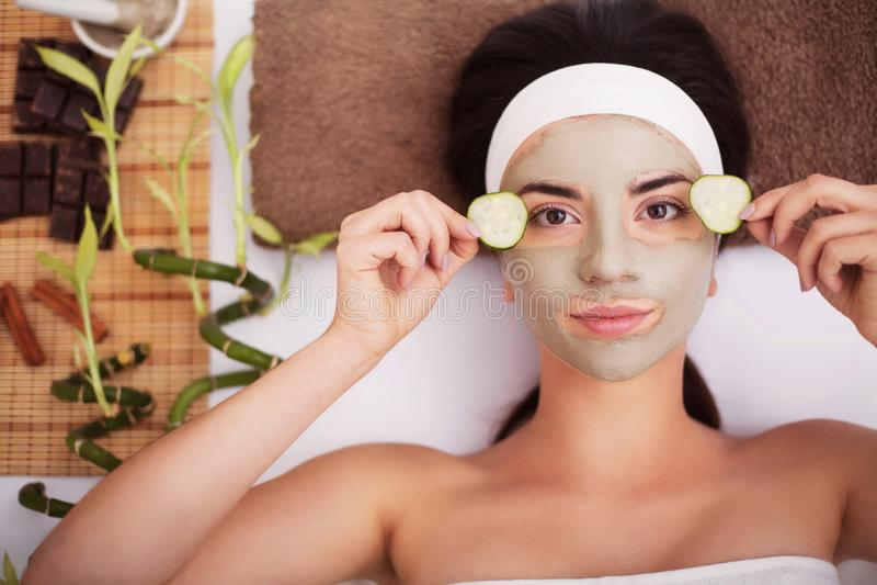 Termas A jovem mulher bonita está obtendo a máscara facial em termas, l da argila foto de stock royalty free