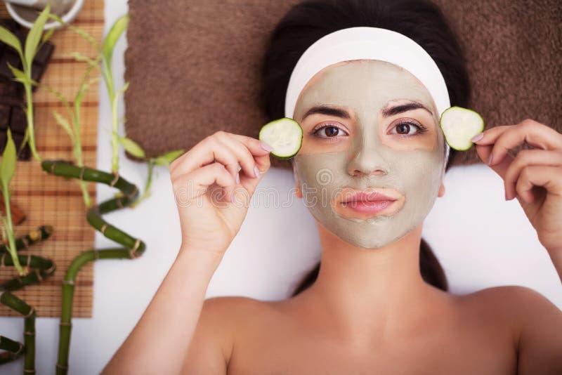 Termas A jovem mulher bonita está obtendo a máscara facial em termas, l da argila imagem de stock