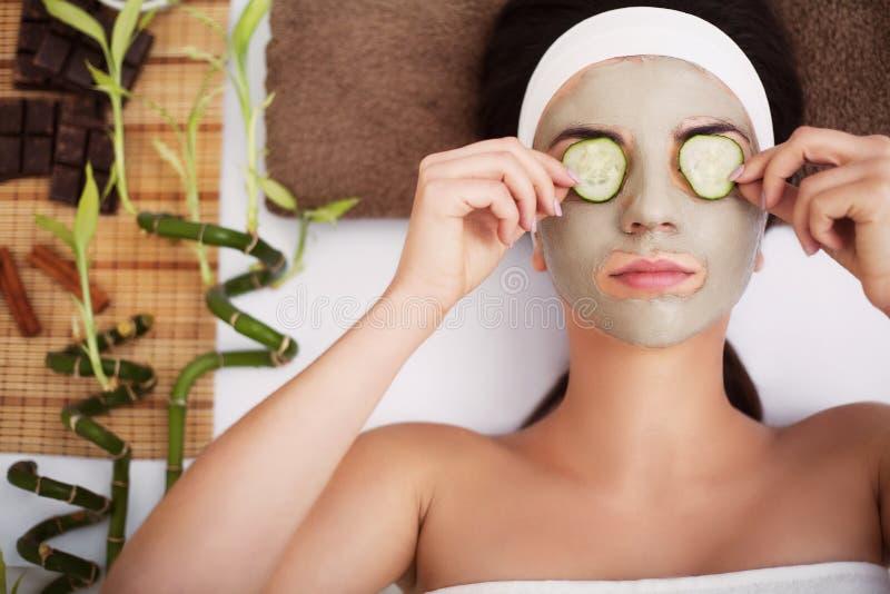 Termas A jovem mulher bonita está obtendo a máscara facial em termas, l da argila imagens de stock