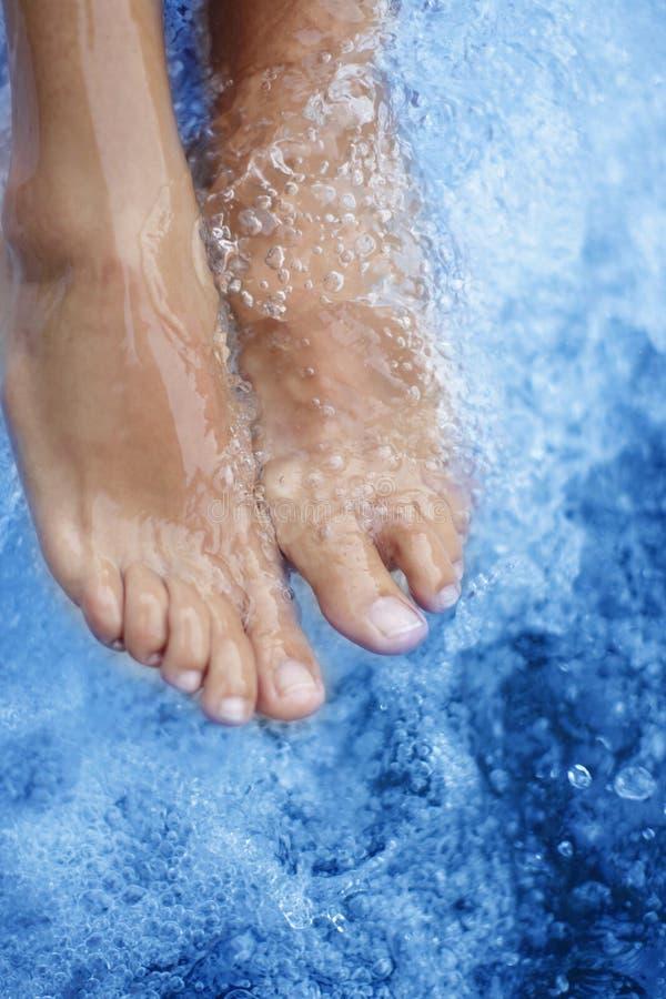 Termas - massagem fêmea do pé com água azul ventilada imagens de stock