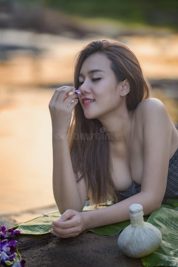 Termas naturais, mulher bonita que relaxa no banho exterior redondo com flores tropicais imagem de stock