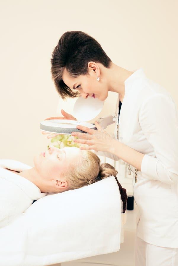 Termas o escritório do cosmetologist da cosmetologia examina a pele moça que encontra-se no sofá imagem de stock royalty free