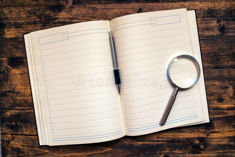 Termin-Tagesordnungsnotizbuch mit Bleistift und Lupe lizenzfreie stockbilder