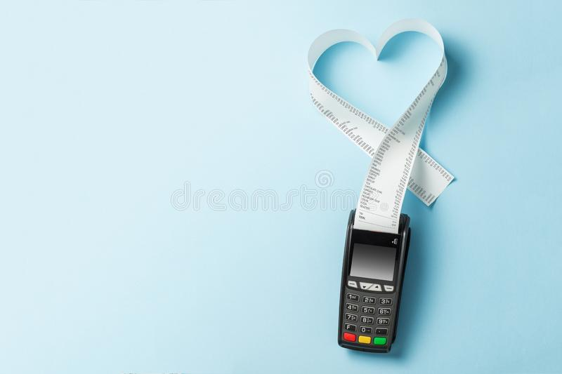 Terminal cash register machine POS for payments and long roll paper cash tape in heart shaped on blue background. Copy space for stock images