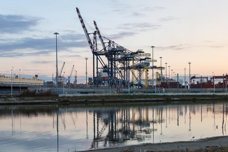 Terminal, chantier naval et grues de récipient chez le coucher du soleil et leur Refl images libres de droits
