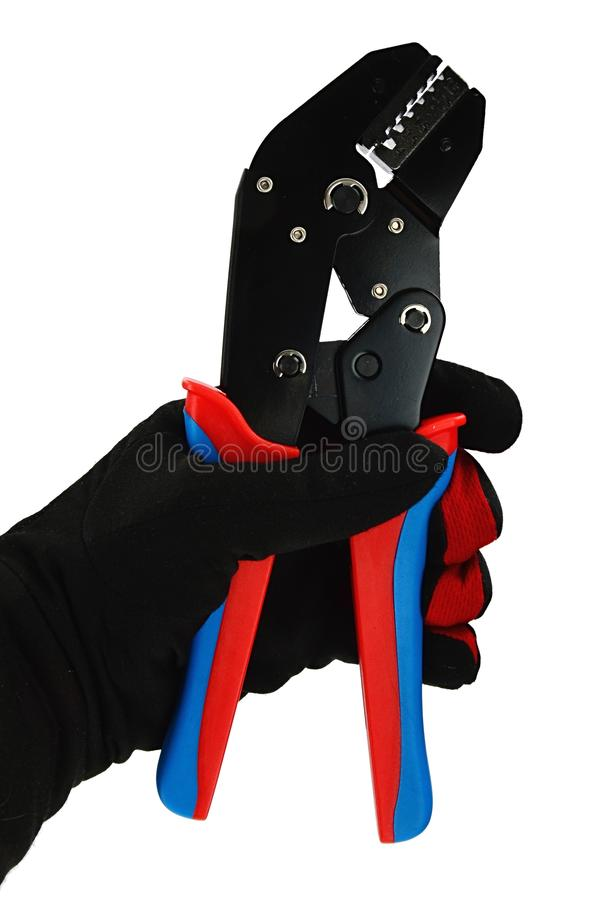 Terminal crimping press pliers with closed jaws, held in left hand in thin black nylon/polyester/spandex glove. White background royalty free stock photography