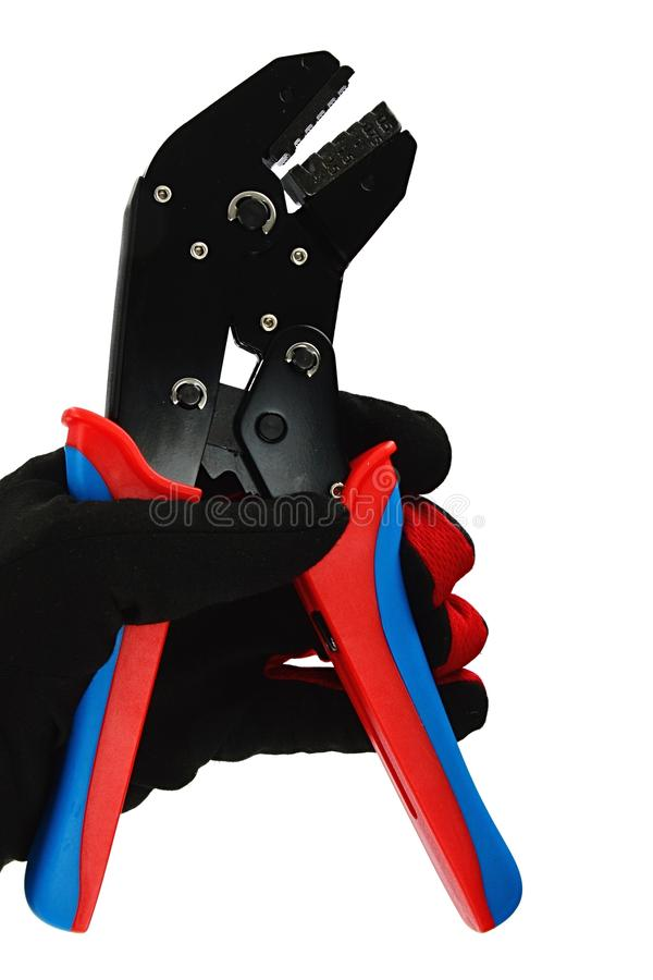 Terminal crimping press pliers with half closed jaws, held in left hand in thin black nylon/polyester/spandex glove. Terminal crimping press pliers with closed royalty free stock image