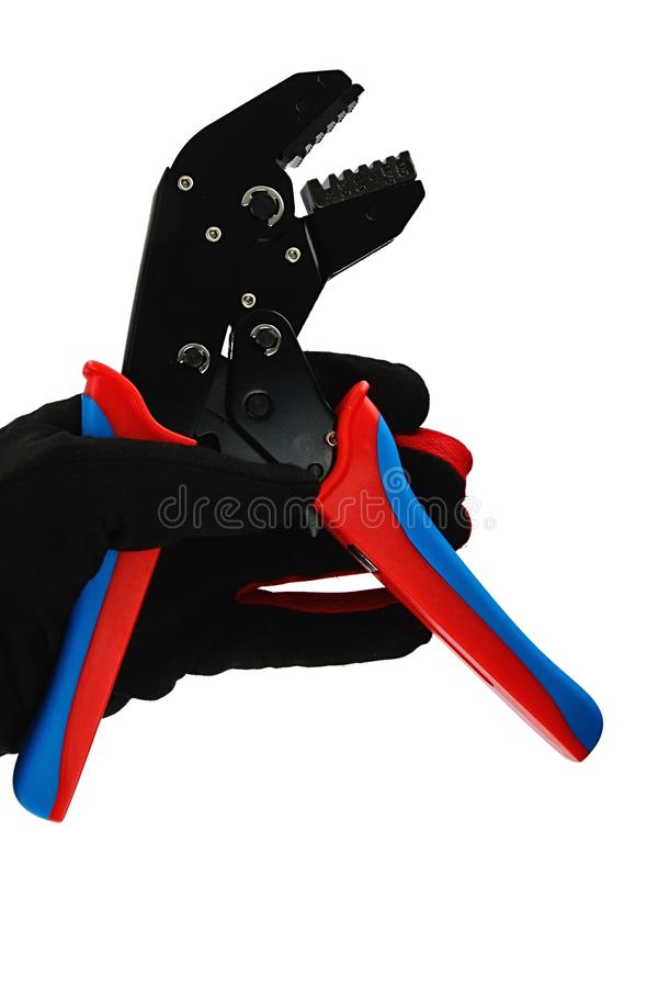 Terminal crimping press pliers with opened jaws, held in left hand in thin black nylon/polyester/spandex glove, white background. Interior light stock images