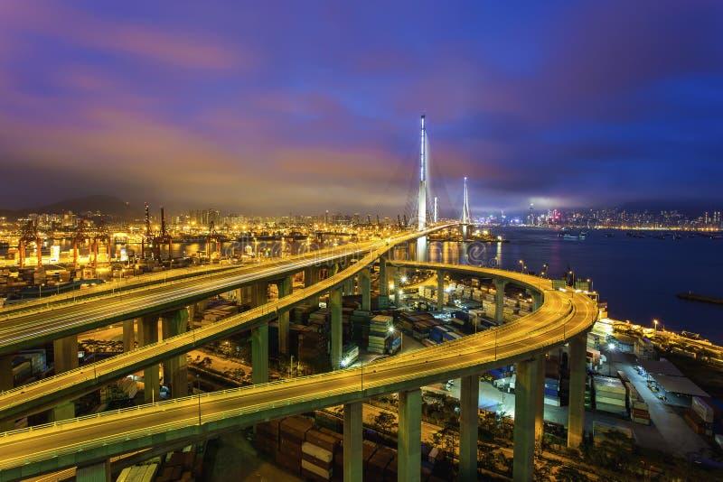 Terminal del cargo a lo largo del puente en la noche imagenes de archivo