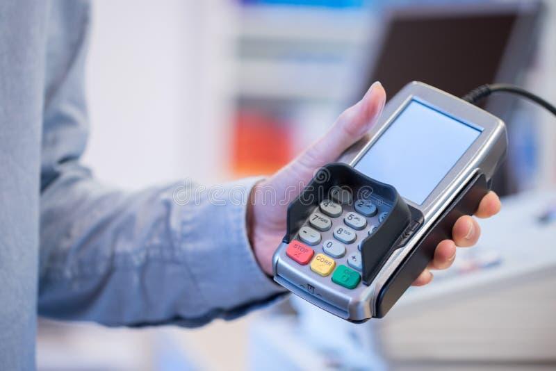 Terminal del pago en una tienda, pagando por la tarjeta foto de archivo